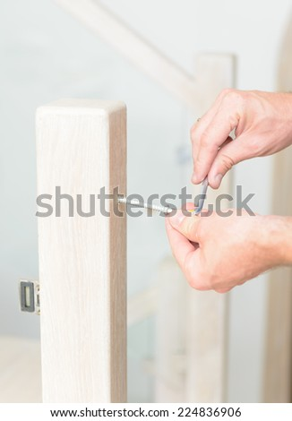 Carpenter working with screwdriver on stairs - stock photo