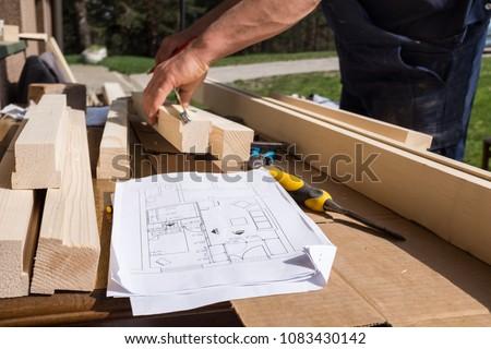 Carpenter working technical drawing blueprint construction stock carpenter working with technical drawing or blueprint construction paper lying on a workshop outdoor desk malvernweather Images