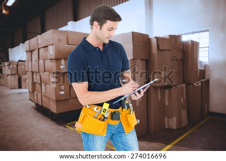 Carpenter writing on clipboard over white background against cardboard boxes in warehouse - stock photo