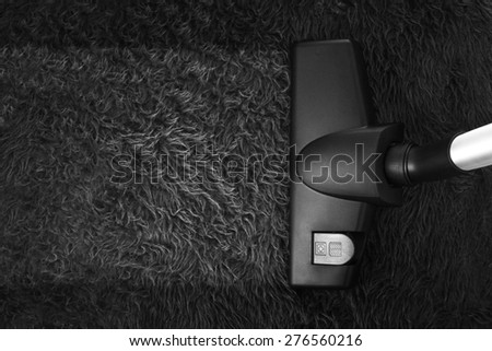 Carpet cleaning with vacuum cleaner and copy space - stock photo
