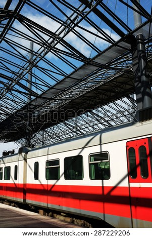 carriages of a passenger train under a glass roof station - stock photo
