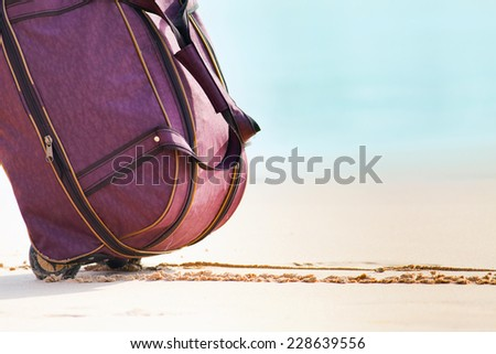 Carries luggage at white sandy beach - stock photo