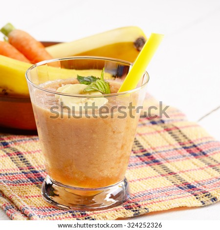 Carrot and banana shake on white table. Smoothie concept