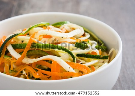 Carrot and zucchini noodles on a rustic wooden table
