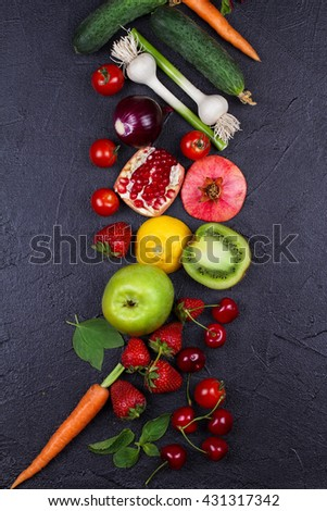 Carrot, beetroot, cucumber, lemon, pomegranate, kiwi, apples, tomatoes, cherries, strawberry, red onion, basil and mint. View from above, top studio shot of vegetables and fruits - stock photo