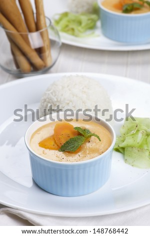 carrot cream soup with rice, cucumber salad and bread sticks set up on table