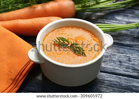Carrot cream-soup with vegetables on table close up - stock photo