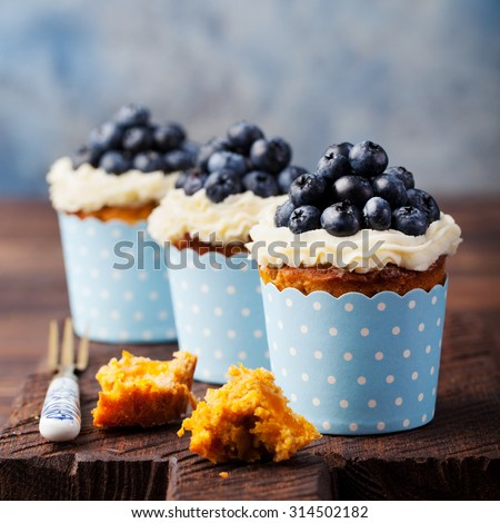 Carrot cupcakes  decorated with cream cheese frosting and fresh blueberries on a wooden background - stock photo