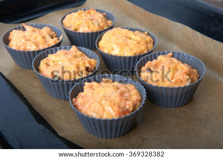 Carrot cupcakes with lemon and apple, nuts and candied fruits on wooden background, raw silicone form on a baking sheet - stock photo