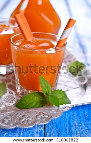 Carrot juice in glass Cup on a wooden surface. Selective focus. - stock photo