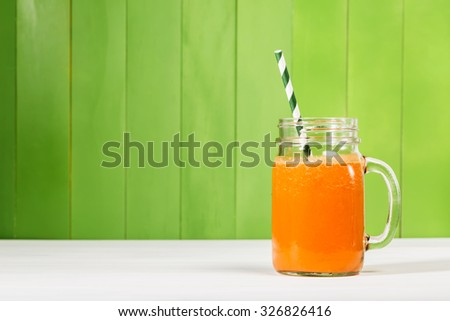 Carrot juice in masons jar on green wooden background - stock photo