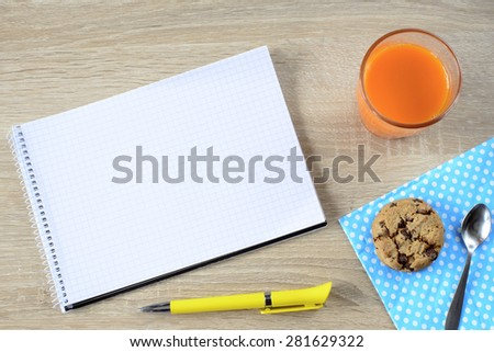Carrot juice with cookie and empty notepad - stock photo