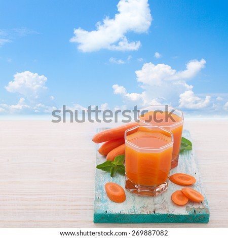 Carrot Juices and vegetables on white wooden table - stock photo