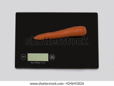 Carrot on a digital white kitchen scale. (weighing products) - stock photo