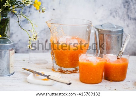 Carrot, orange, banana and papaya detox smoothies drink with iced cubes in carafe glass over white wooden table with summer flowers bunch. Rustic style.