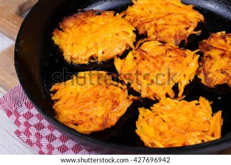 Carrot pancakes in a pan.