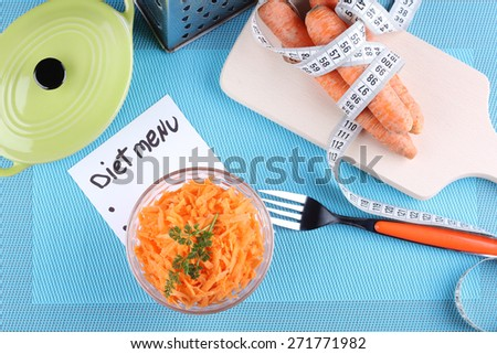 Carrot salad, a bunch of carrots and a cutting board. Diet food, diet plan, diet menu. The concept of diet, diet food. Weight loss, a healthy lifestyle, the concept of healthy eating. - stock photo