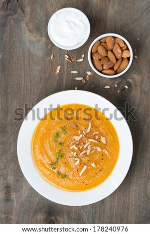 carrot soup with almonds and yogurt, top view, vertical - stock photo