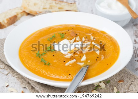 carrot soup with almonds, yogurt and watercress in a plate, close-up - stock photo