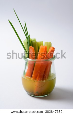 carrots , augures and onions in a glass on white background