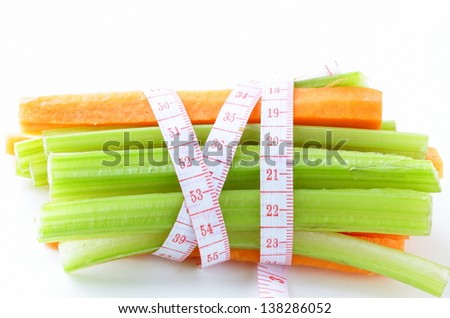 carrots, green celery,  measuring tape on a white background
