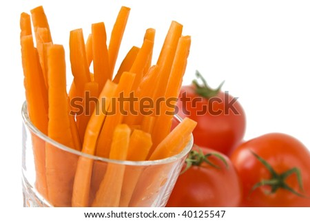 Carrots in a glass with tomatoes isolated on white background.