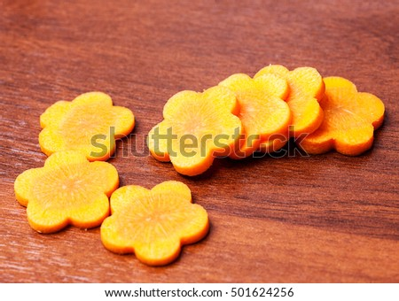 carrots in slices cut into flower shape on wood table