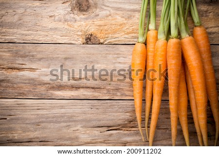 Carrots more on a wooden background. Studio photography.