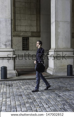 Carrying a leather bag and talking on the phone, a young handsome guy is walking on a old fashion style street. / Walking and Talking  - stock photo