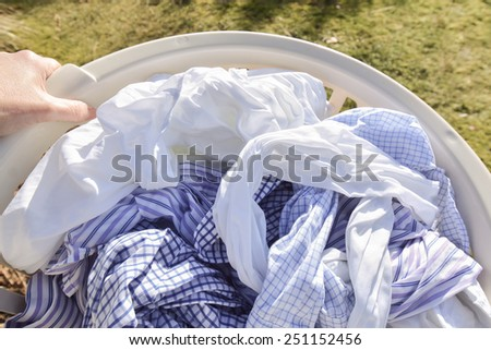 carrying clean wet washing outside to hang out to dry in the fresh air - stock photo