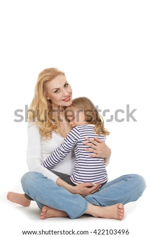 Carrying her angel. Portrait of a happy mature woman looking to the camera cheerfully holding her little sleeping daughter at the studio on white background. - stock photo