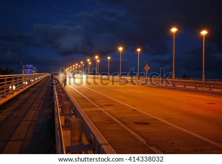 Cars and a bike rider travel at twilight on the 17th Street Causeway Bridge in Fort Lauderdale, Florida.   - stock photo