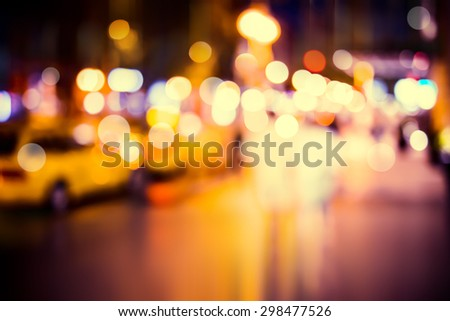 Cars and walking people on the street in the city at night with blurred background - stock photo