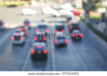 Cars and walking people on the street in the city at with blurred background