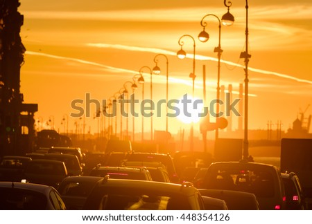 Cars are in a traffic jam during a beautiful golden sunset in a big city. - stock photo