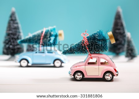 Cars carrying Christmas trees in a snow covered miniature evergreen forest - stock photo