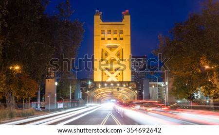 Cars come and go from the Tower Bridge at night in Sacramento - stock photo