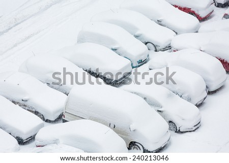 Cars covered in snow on a parking lot in the residential area during December snowfall - stock photo