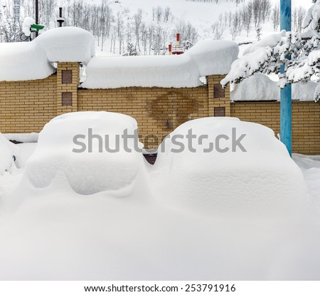 Cars covered with snow in the parking lot in rural mountain area - stock photo