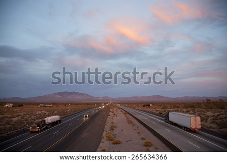 Cars drive Interstate 15 at sunset at California Nevada border looking east  - stock photo