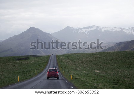 cars driving on a straigth road heading into the distance towards nearby mountains under overcast sky - stock photo
