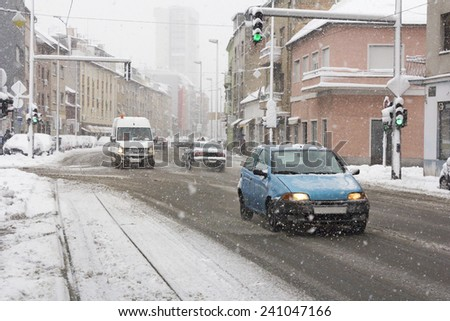 Cars driving on roadway in snow storm in the city - stock photo