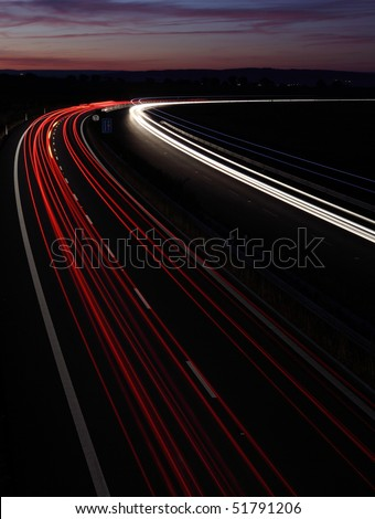 Cars in a rush moving fast on a highway (speedway) at dusk - stock photo