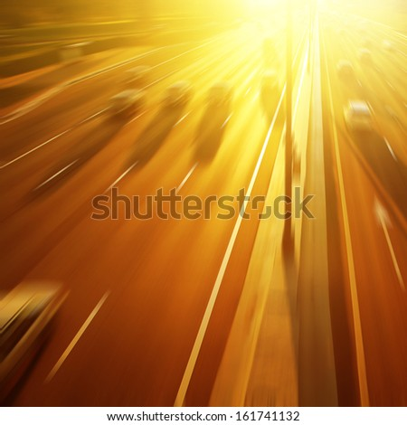 Cars in motion blur on highway at sunset. - stock photo