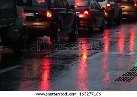 cars in traffic jam on wet road at rainy city evening - stock photo