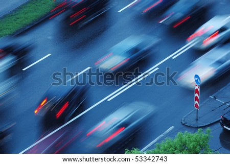 Cars moving over wet road background. Blurred motion. - stock photo