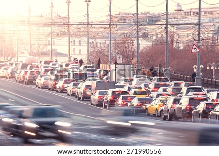 Cars on the road on the central city street at sunset time. - stock photo