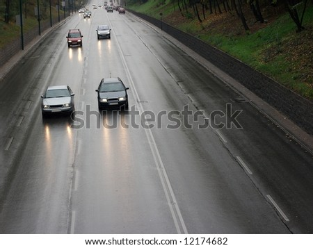 Cars passing by on a wet rainy road - stock photo