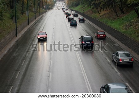 Cars passing by on a wet road in the rain - stock photo