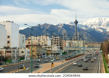 Cars passing in a highway of Tehran with Milad Tower and Alborz Mountains in the background.